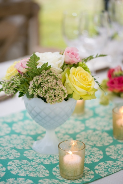 Wedding table topped with milk glass flower centerpieces and crafted glitter votives.