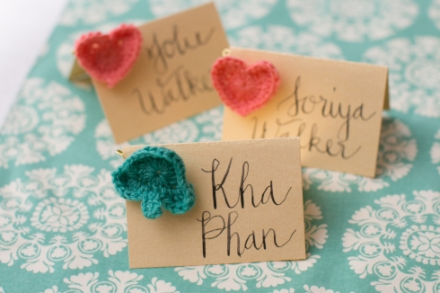 Hand-written escort cards with crocheted hearts and spades.