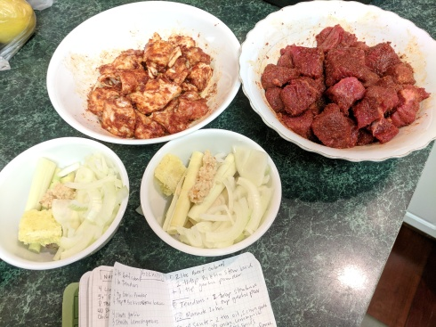 Marinating beef and tendon with bowls of onion, garlic, lemongrass and ginger