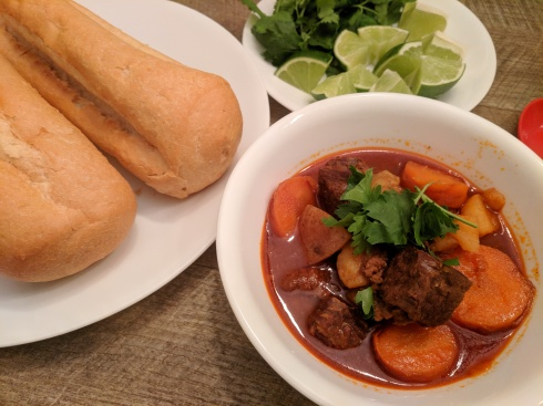 French bread, bowl of Vietnamese beef stew Bo Kho with plate of limes and cilantro
