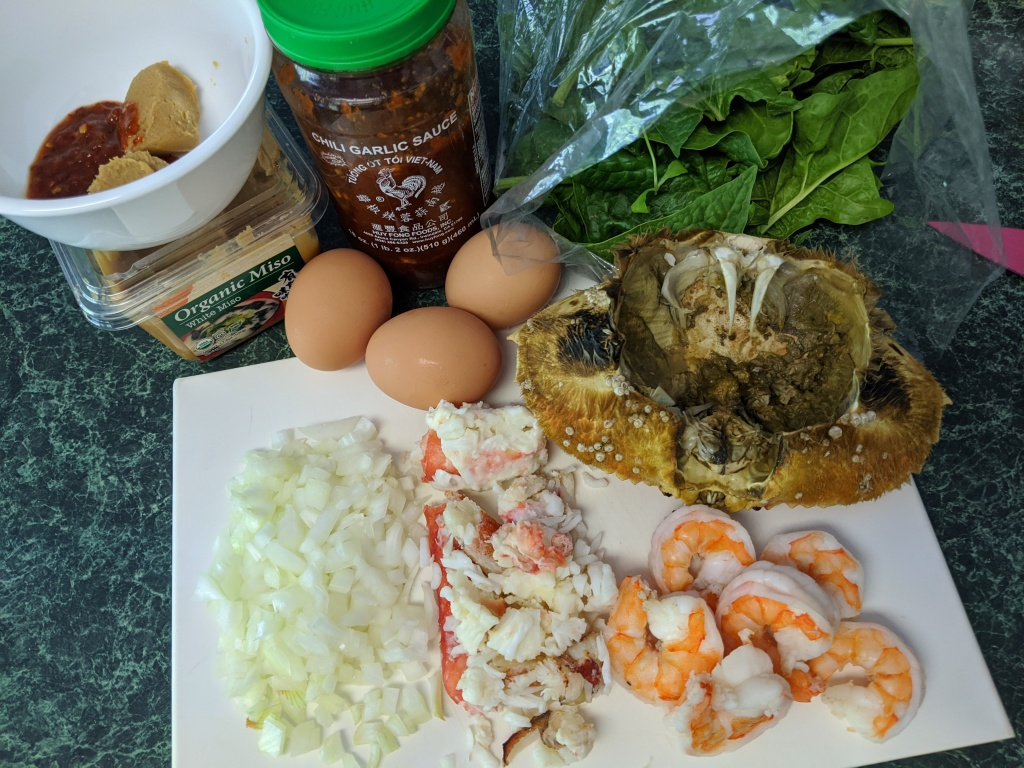 Ingredients for pasta including chili garlic sauce, miso paste, eggs, spinach, Dungeness crab fat, shrimp, crab meat, and diced onion