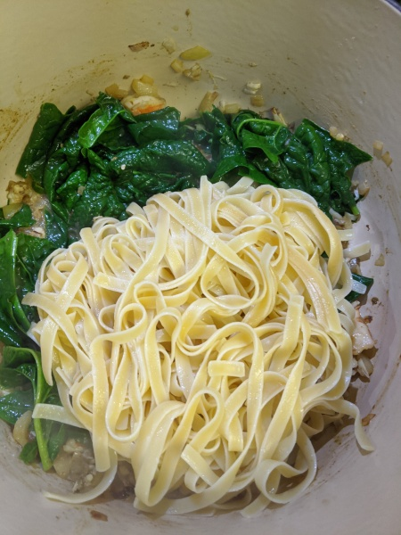 Adding fettuccine pasta and spinach to pan cooking with onion, crab, and shrimp.