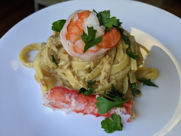 Finished plate of fettuccine pasta with crab and shrimp garnished with parsley
